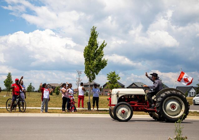 People watch from the sidewalk as a drive-by parade makes its away around town, during Canada Day celebrations in Newcastle, Ontario, Canada July 1, 2020.