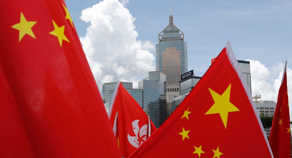 Buildings are seen above Hong Kong and Chinese flags, as pro-China supporters celebration after China's parliament passes national security law for Hong Kong, in Hong Kong, China June 30, 2020.