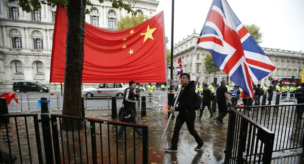 A supporter of Chinese President Xi Jinping carries a large British flag past the national flag of China outside Downing Street  where he is meeting the British Prime Minister David Cameron in London, Wednesday, Oct.  21, 2015