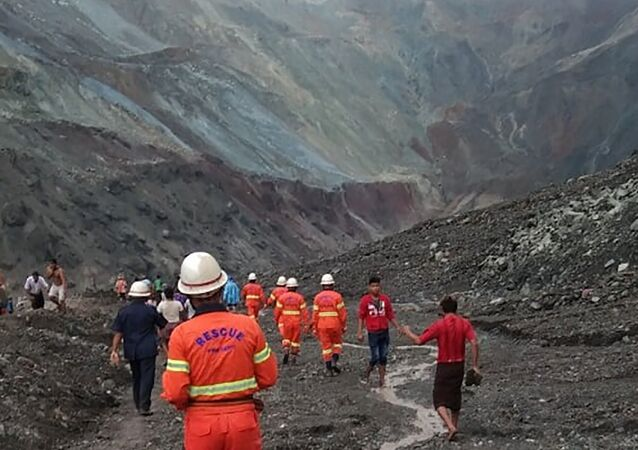 This handout from the Myanmar Fire Services Department taken and released on July 2, 2020 shows rescuers attempting to locate survivors after a landslide at a jade mine in Hpakant, Kachin stat