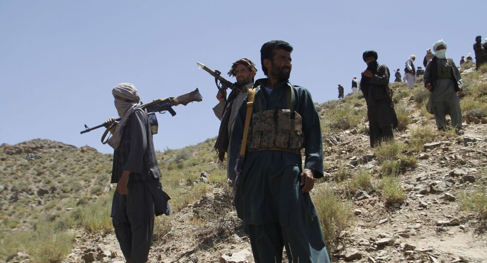 In this Friday, May 27, 2016 photo, Taliban fighters stand guard as senior leader of a breakaway faction of the Taliban Mullah Abdul Manan Niazi, not pictured, delivers a speech to his fighters, in Shindand district of Herat province, Afghanistan