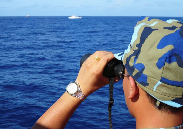 A crewman from the Vietnamese coastguard ship 8003 looks out at sea as Chinese coastguard vessels give chase to Vietnamese ships that came close to the Haiyang Shiyou 981, known in Vietnam as HD-981, oil rig in the South China Sea, July 15, 2014.