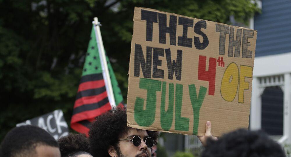 A protester in Seattle holds a banner saying This the new 4th of July during a march on Juneteenth - June 19.