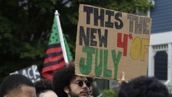 A Black Lives Matter activist holds a banner warning of a new 4th of July - Sputnik International