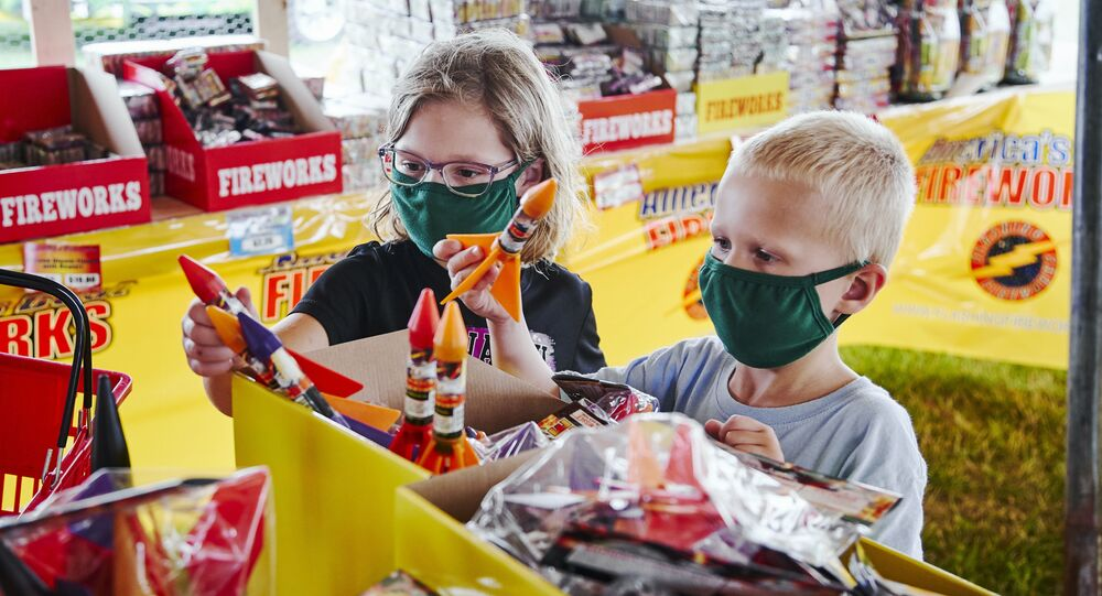 Children wear face masks as they pick out fireworks in Omaha, Nebraska ahead of the 4th of July holiday.