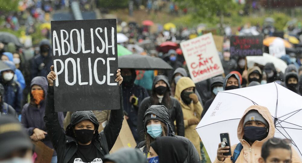 A protester holds a sign that reads Abolish Police during a Silent March against racial inequality and police brutality that was organized by Black Lives Matter Seattle-King County, Friday, June 12, 2020, in Seattle