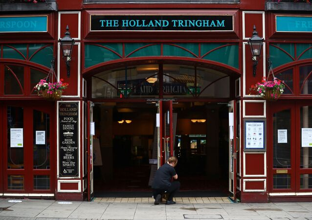 A staff member opens the doors of The Holland Tringham Wetherspoons pub