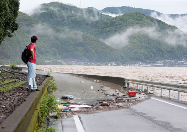 A man looks at the overflowing kuma river caused by heavy rain in Yatsushiro, Kumamoto prefecture on July 4, 2020. - Some 75,000 people were ordered to evacuate in western Japan on July 4 as record heavy rain triggered floods and landslides, local media and officials said. The nation's weather agency issued the highest level of heavy rain warnings to Kumamoto and Kagoshima on Kyushu island.