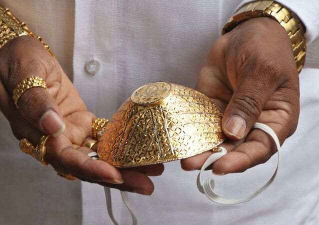 Shankar Kurhade (48), shows his face mask made out of gold
