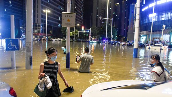 People wade through floodwater at an intersection after heavy rainfall led to flooding in Hefei, Anhui province, China, 27 June 2020 - Sputnik International