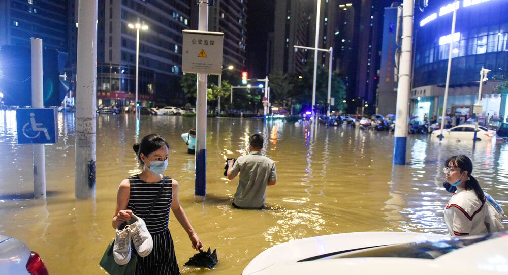 People wade through floodwater at an intersection after heavy rainfall led to flooding in Hefei, Anhui province, China, 27 June 2020