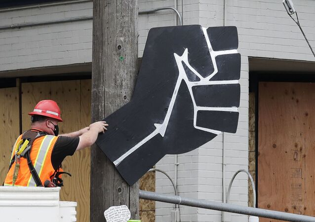A worker removes a rendering of a clenched fist from a Seattle police precinct Wednesday, July 1, 2020, in Seattle, where streets had been blocked off in an area demonstrators had occupied for weeks. Seattle police showed up in force earlier in the day at the occupied protest zone, tore down demonstrators' tents and used bicycles to herd the protesters after the mayor ordered the area cleared following two fatal shootings in less than two weeks. The Capitol Hill Occupied Protest zone was set up near downtown following the death of George Floyd while in police custody in Minneapolis.