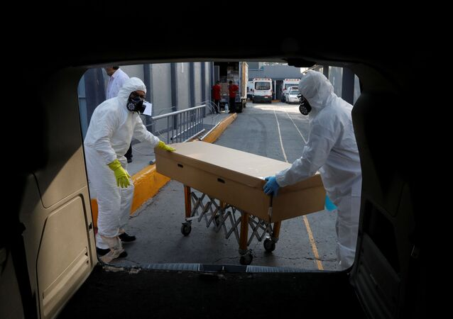 Funeral workers transport the body of a person who died of the coronavirus disease (COVID-19) inside a cardboard coffin, after collecting it from a hospital in Mexico City, Mexico June 5, 2020.