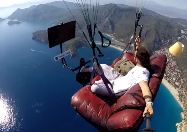 A screenshot of a video of Hasan Kaval, a Turkish paragliding instructor, watching TV while flying over water on a couch attached to a paraglider.