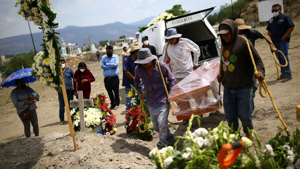 Cemetery workers carry the coffin containing the body of Juana, 50, who died of the coronavirus disease (COVID-19) next to a grave at the Xico cemetery on the outskirts of Mexico City, Mexico, June 10, 2020.  - Sputnik International