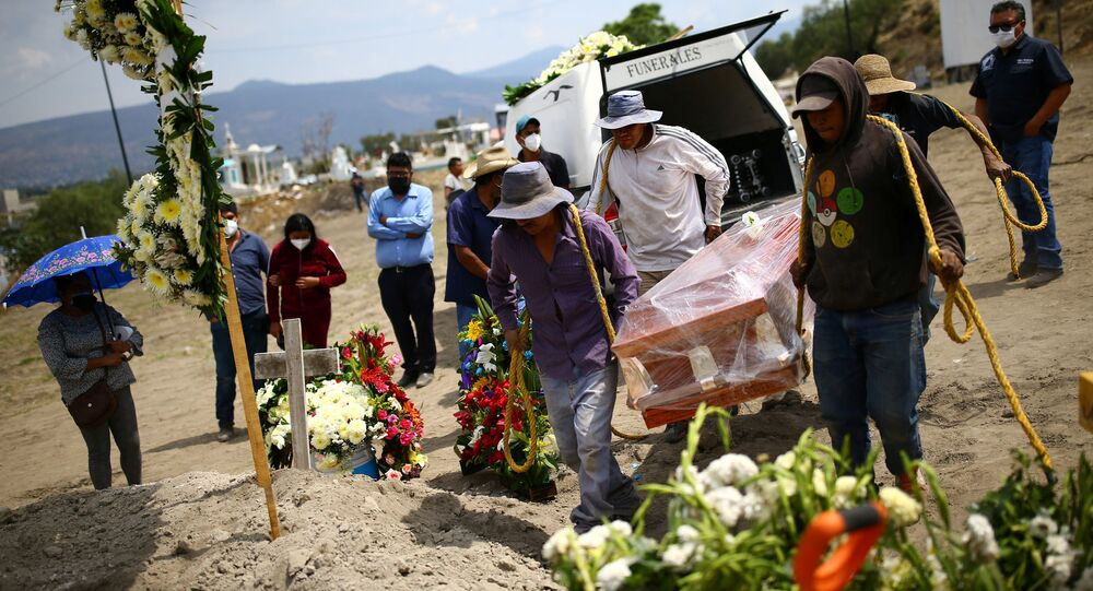 Cemetery workers carry the coffin containing the body of Juana, 50, who died of the coronavirus disease (COVID-19) next to a grave at the Xico cemetery on the outskirts of Mexico City, Mexico, June 10, 2020.