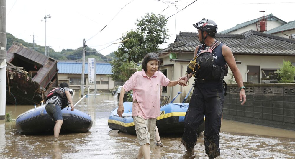 A rescue worker helps local residents at a flooded area caused by heavy rain along Kuma River in Hitoyoshi, Kumamoto prefecture, southern Japan, in this photo taken by Kyodo 4 July 2020