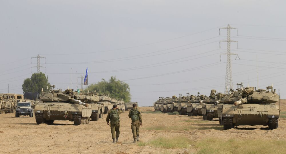 Israeli soldiers walk past tanks in a gathering point near Israel Gaza border, Friday, Oct. 19, 2018.