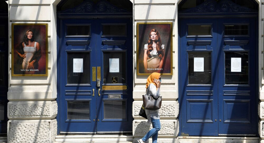 A woman wearing a protective face mask walks past a closed theatre following the spread of the coronavirus disease (COVID-19) in London, Britain June 23, 2020