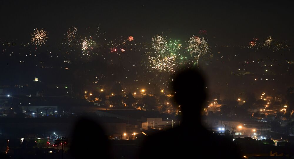 People watch fireworks burst over Los Angeles, California on 4 July 2020 during celebrations for the Fourth of July holiday, amid the coronavirus pandemic.