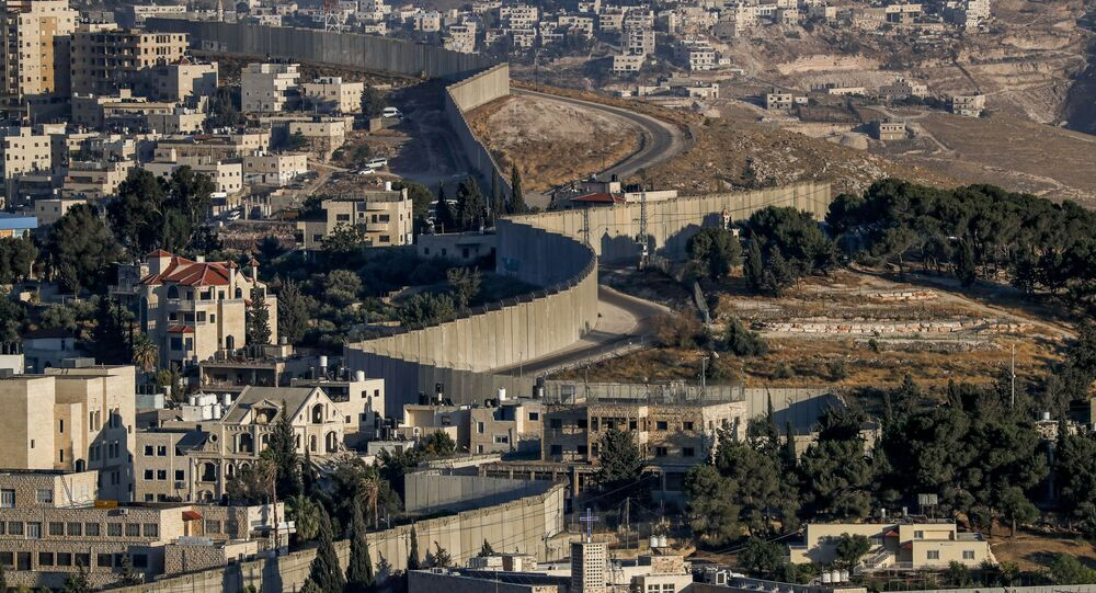 This picture taken on 30 June 2020 shows a view of Israel's controversial separation barrier between the West Bank city of Abu Dis (L) and East Jerusalem (R).