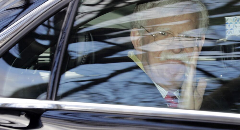 Former National security adviser John Bolton waves as he leaves his home in Bethesda, Md. Tuesday, Jan. 28, 2020