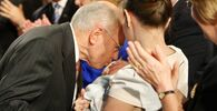 Australian Prime Minister John Howard (L) kisses the head of his grandson, Angus Howard-McDonald (C) who is being held by daughter Melanie (R) at the Coalition campaign launch in Brisbane, 12 November 2007.  Australian Prime Minister John Howard is headed for a landslide defeat at elections next week, according to an opinion poll released 12 November which showed the opposition surging ahead.  The centre-left Labor Party gained two percentage points over the past week to extend its lead over Howard's conservative Liberal-National coalition to 55 percent against 45 percent, the Newspoll showed.