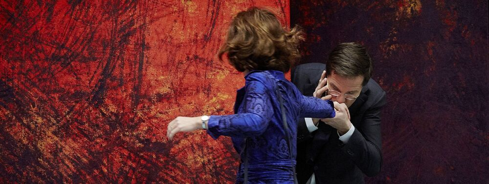 The Netherlands' Prime Minister Mark Rutte (R) kisses chamber chair Anouchka van Miltenburg on the hand before the start of the debate about the calendar for the European Summit on 18 December 2013.