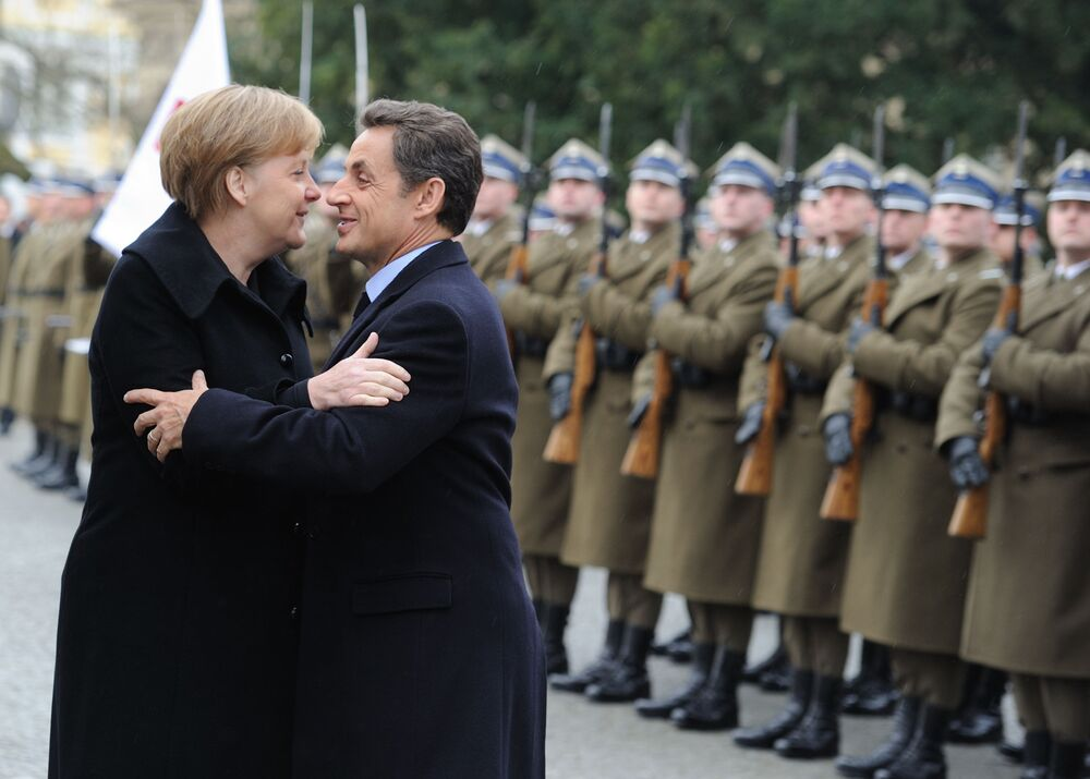 German Chancellor Angela Merkel (L) and French President Nicolas Sarkozy kiss each other upon their arrival at  Wilalow Palace on 7 February  2011 in Warsaw for the Weimar Triangle summit.