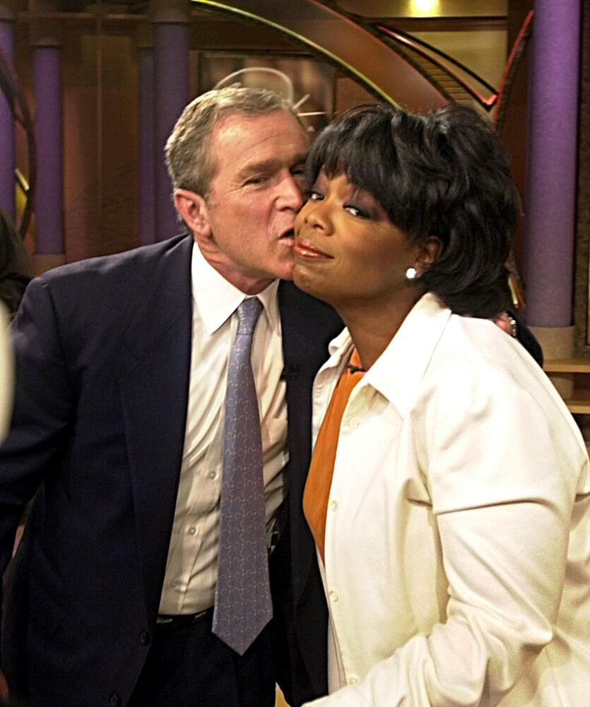 Republican presidential nominee Texas Gov. George W. Bush gives a kiss to Oprah Winfrey after appearing on her show on 19 September 2000 in Chicago, Illinois.