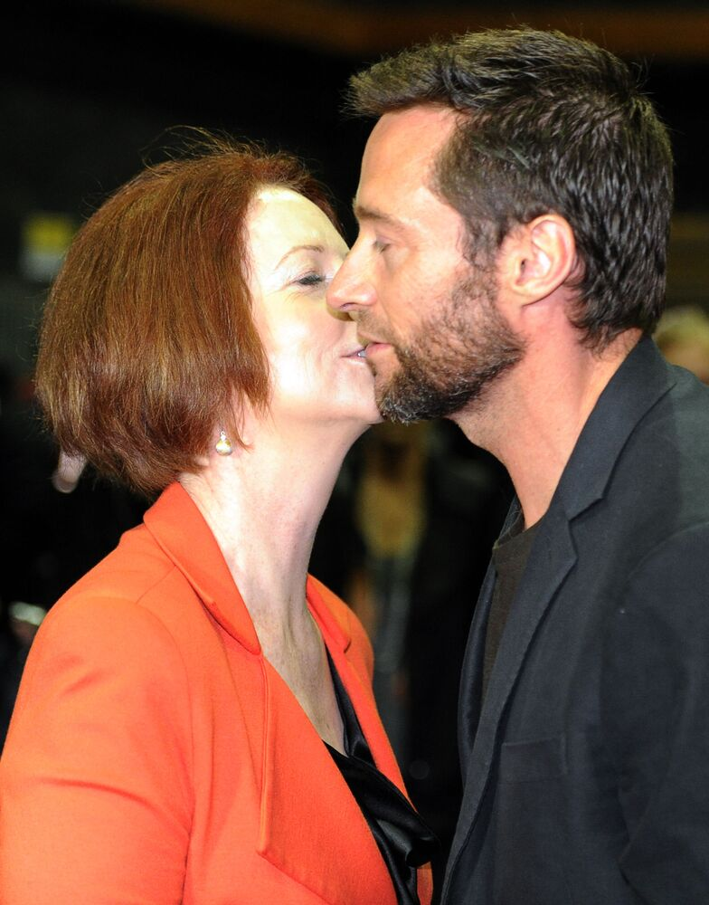 Actor Hugh Jackman (R) and Australian Prime Minister Julia Gillard (L) kiss on the set of the movie 'The Wolverine' in Sydney on 24 July 2012.  The Wolverine sees Jackman reprise his most famous role as the superhero with metal claws and will be shot in Sydney after a 13.2 million USD grant from the Australian government.