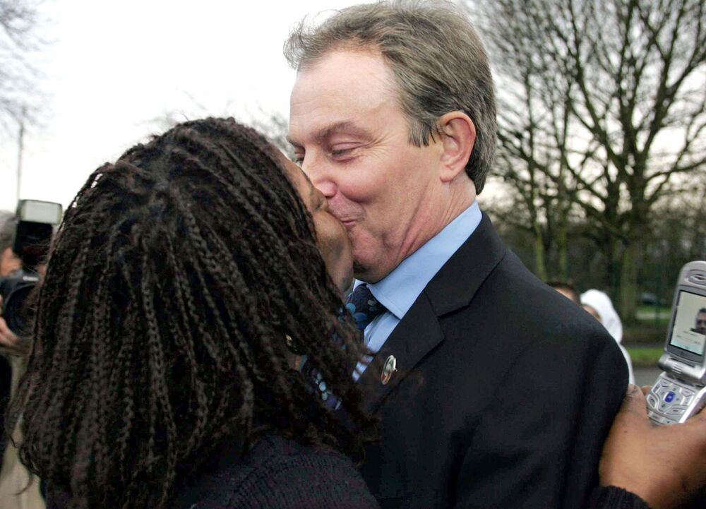 Prime Minister Tony Blair is kissed by Jean Peterson during a visit to Wythenshawe, near Manchester, England, 31 January 2005.