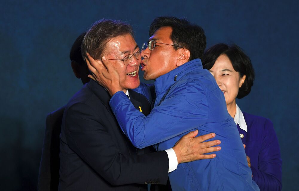 South Korean presidential candidate Moon Jae-in (L) of the Democratic Party receives a kiss from his party member Ahn Hee-Jung (R), who was a presidential candidate contender of the Party, as they gather to watch broadcast of the presidential election results at a park near the presidential Blue House in Seoul on 9 May 2017.
