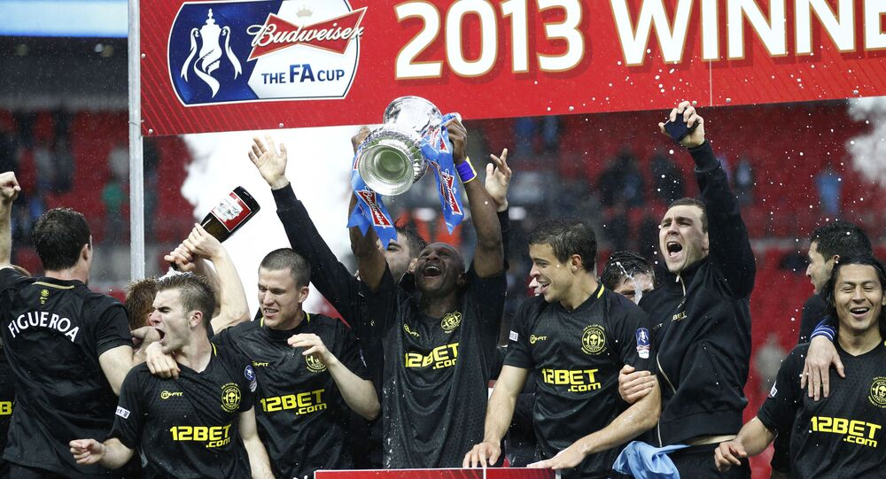Wigan Athletic captain Emmerson Boyce holds up the FA Cup after they defeated Manchester City in the 2013 final