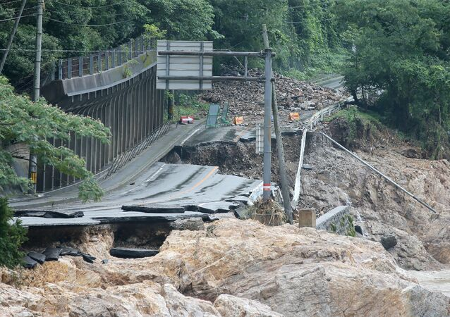 A road is destroyed following torrential rain near the Kuma river in Ashikita, Kumamoto prefecture, on July 6, 2020. -