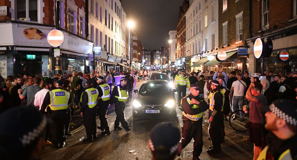 Police officers move revellers from the road to allow traffic to pass in the Soho area of London on July 4, 2020, after the police re-opened the road at 2300 following a further easing of restrictions to allow pubs and restaurants to open during the novel coronavirus COVID-19 pandemic.
