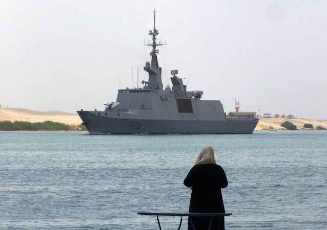 An Egyptian woman looks at the French frigate Courbet crossing the Suez Canal waterway near the port city of Ismailia, east of Cairo, on April 19, 2013.