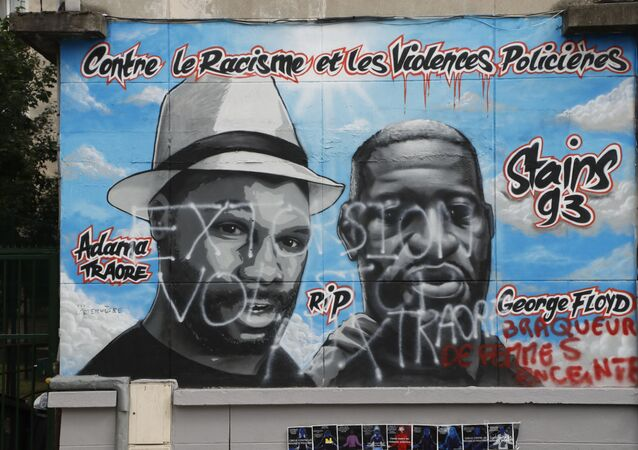 A photograph taken on July 5, 2020 shows a vandalised graffiti created by a French artist collective Collectif Art reading Against racism and police violence and paying tribute to George Floyd (R), an African american killed by a police officer in Minneapolis on May 25, 2020 and Adama Traore (L) a black man who died in police custody in 2016, on a wall in a street of Stains, in the outskirts of Paris. - The graffiti in memory of George Floyd and Adama Traore has been vandelised overnight on July 5, 2020 said a source from the prefecture.