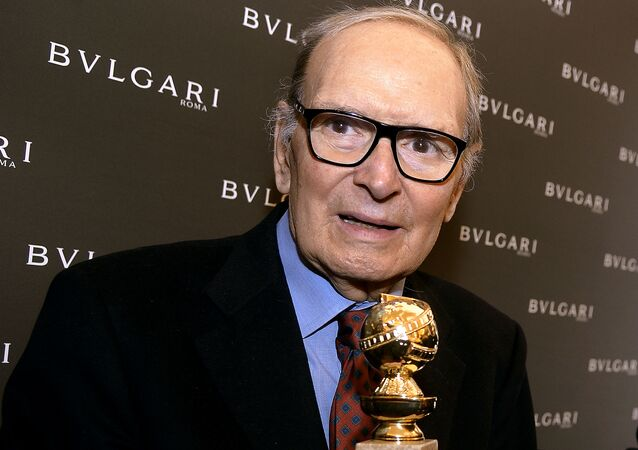 In this file photo taken on January 30, 2016 Italian composer Ennio Morricone poses with the 2016 Golden Globe for Best Original Score for Quentin Tarantino's hit movie The Hateful Eight during a press conference at Bulgari Domus in central Rome on January 30, 2016.