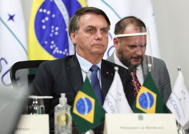 Handout picture released by Brazil's Presidency showing Brazilian President Jair Bolsonaro (L) taking part in the first Mercosur Summit held via video conference due to the COVID-19 novel coronavirus pandemic, from Brasilia, on July 2, 2020.