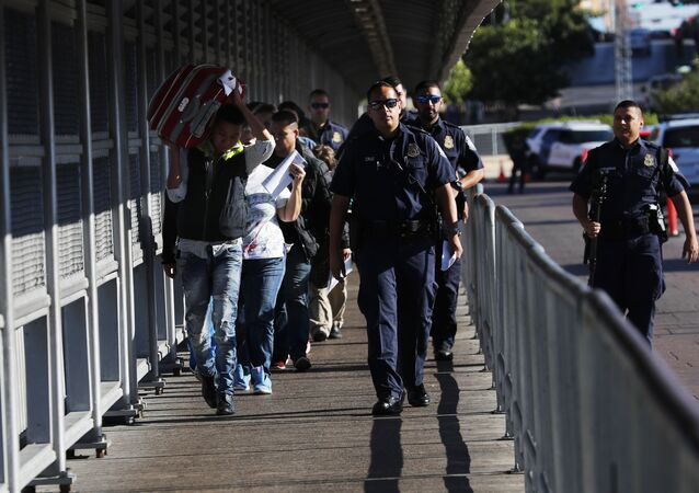 US Customs and Border Protection agents and Central American migrants on International Bridge 1 Las Americas