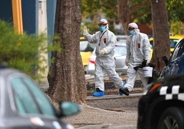 People in hazardous material overalls are seen outside of a public housing tower along Racecourse Road that was placed under lockdown due to the coronavirus disease (COVID-19) outbreak in Melbourne, Australia, July 6, 2020.