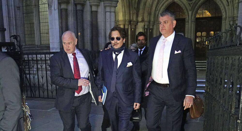Actor Johnny Depp, centre, leaves the High Court in London, after attending a preliminary hearing in his libel case against the publishers of The Sun and its executive editor, Dan Wootton, over a 2018 article alleging he had been abusive to his ex-wife Amber Heard, 26 February 2020.