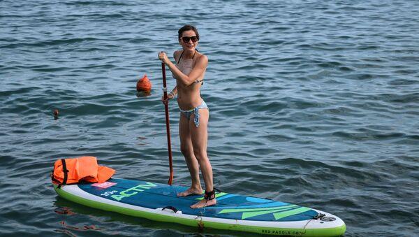 A girl enjoys standup paddleboarding in Sochi - Sputnik International