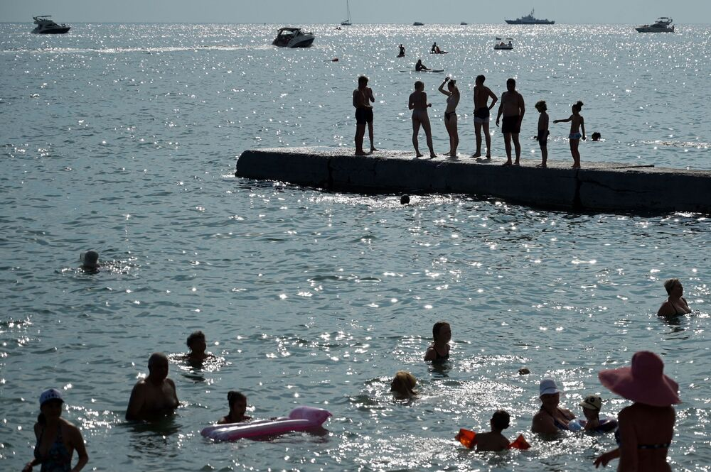 People enjoy a warm summer day on a beach, in the Black Sea resort of Sochi, Russia.