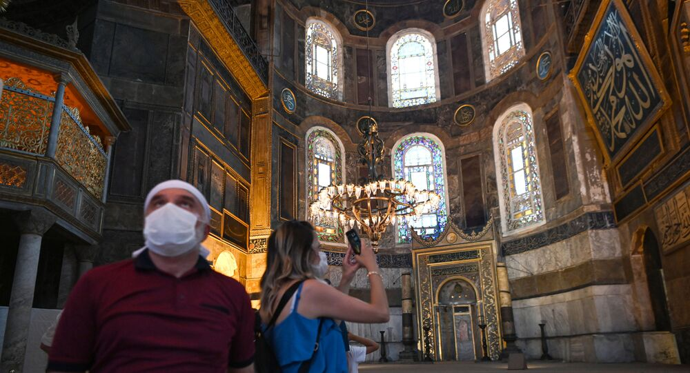 A woman takes a picture with mobile phone inside the Hagia Sophia museum in Istanbul, on July 2, 2020. - Turkey's top court considered whether Istanbul's emblematic landmark and former cathedral Hagia Sophia can be redesignated as a mosque, a ruling which could inflame tensions with the West.