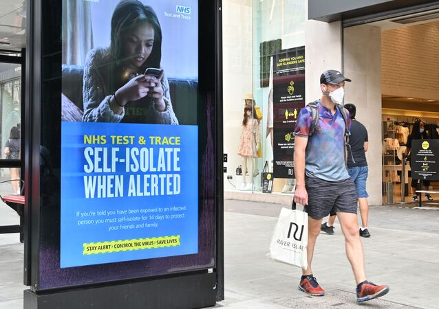A shopper walks past an advertisement for the UK government's NHS Test and Trace system in Regent Street in London on 15 June 2020 as some non-essential retailers reopen from their coronavirus shutdown. - Various stores and outdoor attractions in England are set to open Monday for the first time in nearly three months, as the government continues to ease its coronavirus lockdown.