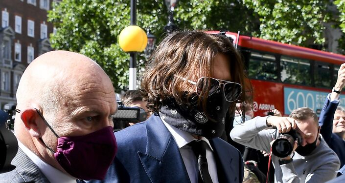 Johnny Depp, centre, wearing a protective mask arrives at the High Court in London for the start of his libel action against The Sun.