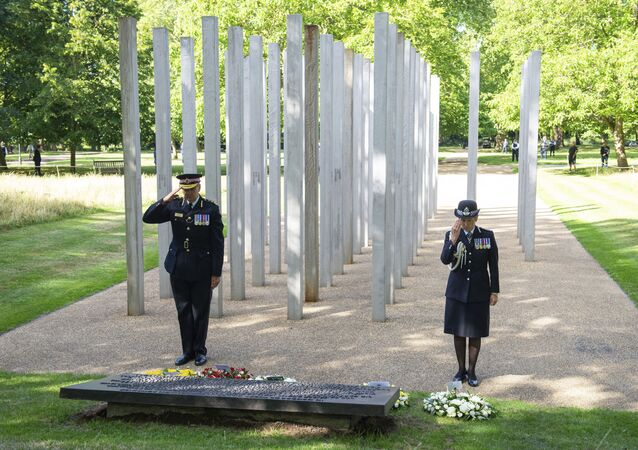 Commissioner of City of London Police Ian Dyson, left, and Metropolitan Police Commissioner Cressida Dick lay a wreath at the 7 July Memorial in Hyde Park, London, Tuesday July 7, 2020, on the 15th anniversary of the attack on the capital