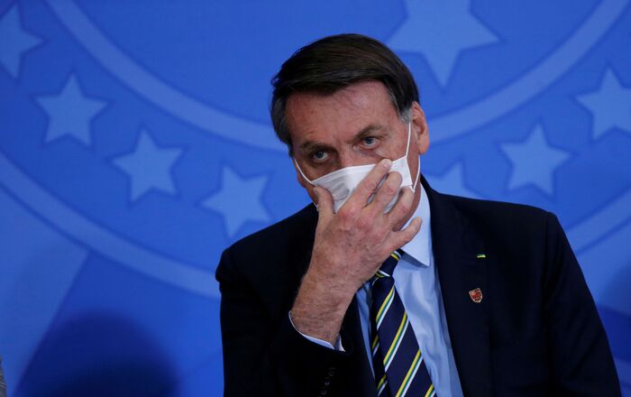 Brazil's President Jair Bolsonaro adjusts his protective face mask during the inauguration ceremony of the new Communications Minister Fabio Faria (not pictured) at the Planalto Palace, in Brasilia, Brazil June 17, 2020